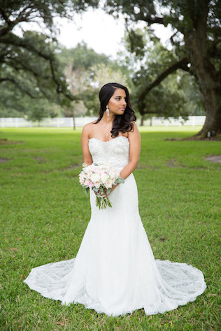 bride holding bouquet in a sweetheart neckline strapless dress