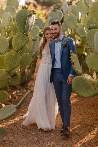 bride and groom walking through cactus