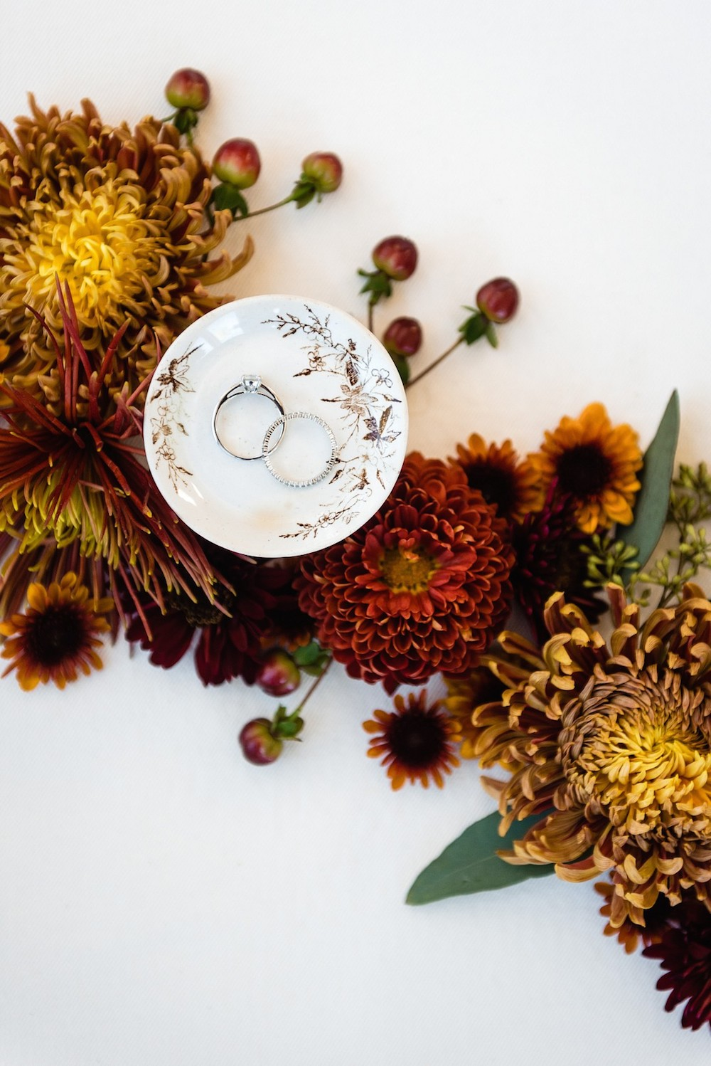 rings in ring dish with flowers in a flat lay