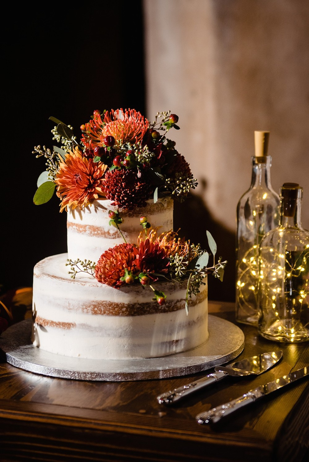 tiered wedding cake with fall colored flowers cascading down the side of it