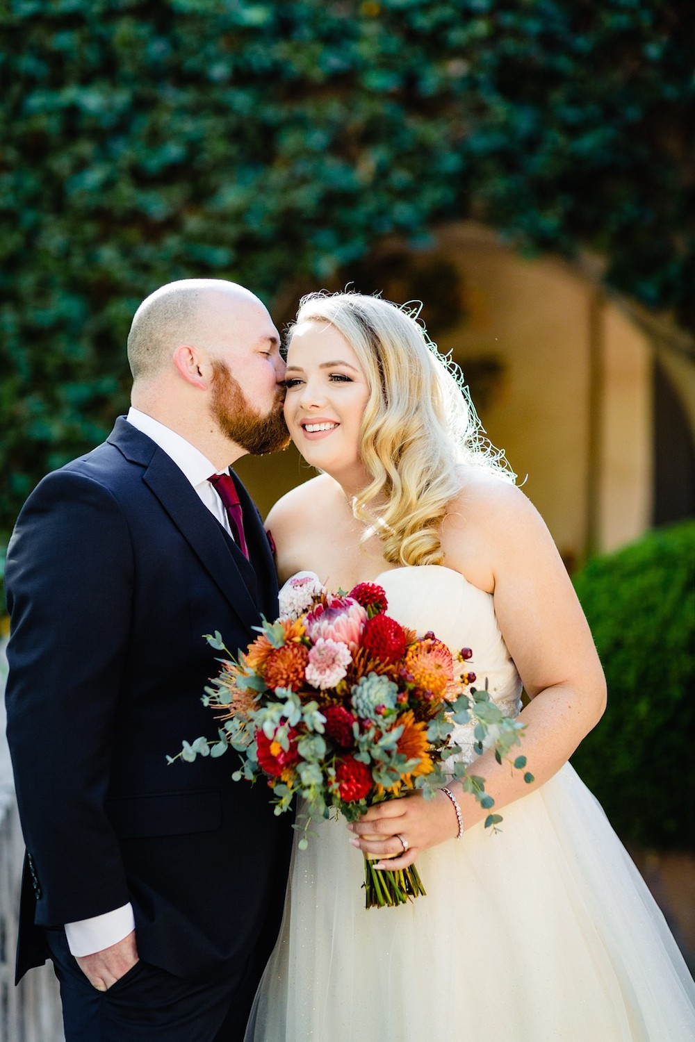 Bride being kissed on the cheek by her groom holding a colorful bouquet of flowers
