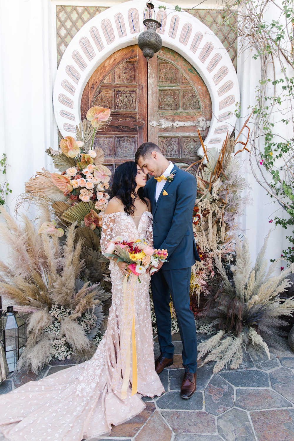 couple in front of pampas grass altar at wedding