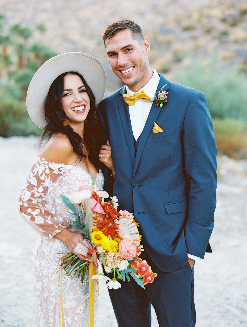 wedding couple bride in hat and groom in navy suit in palm springs
