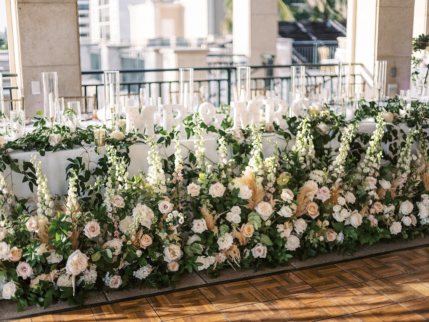 head table at a wedding covered in greenery and flowers