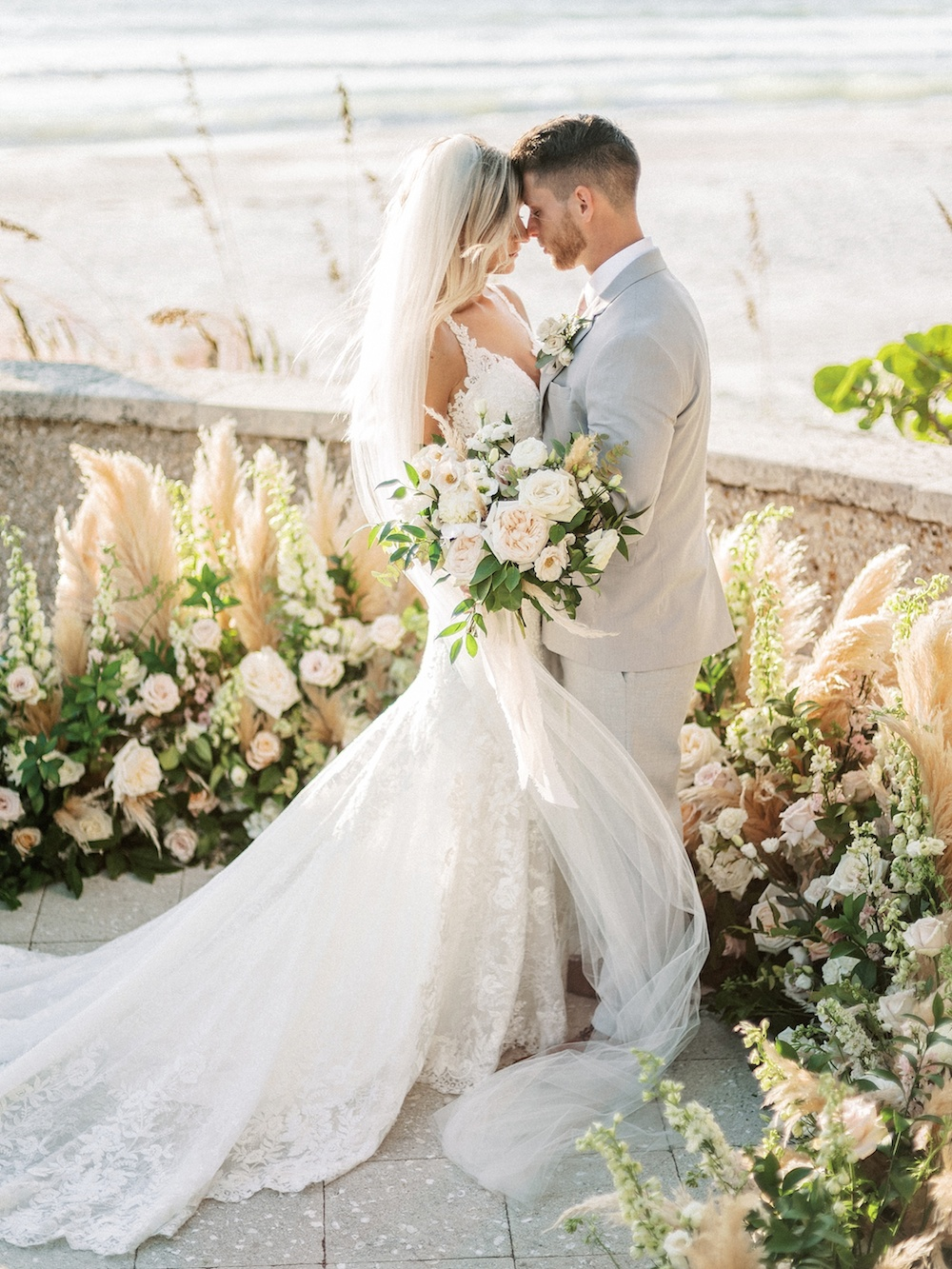 wedding couple surrounded by pampas grass standing by the ocean