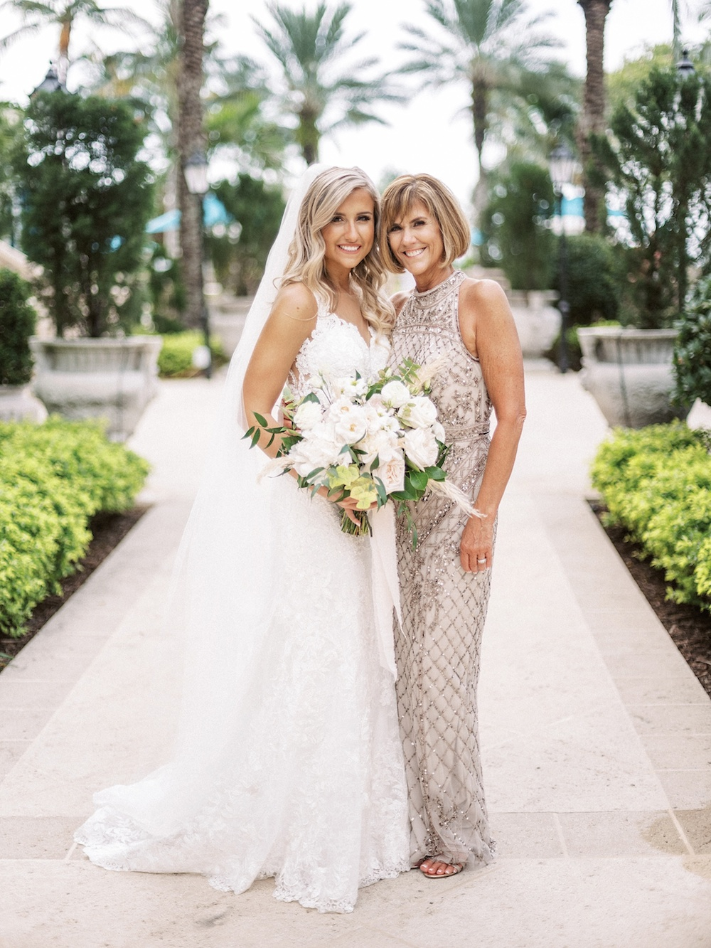 mother and daughter standing together on brides wedding day