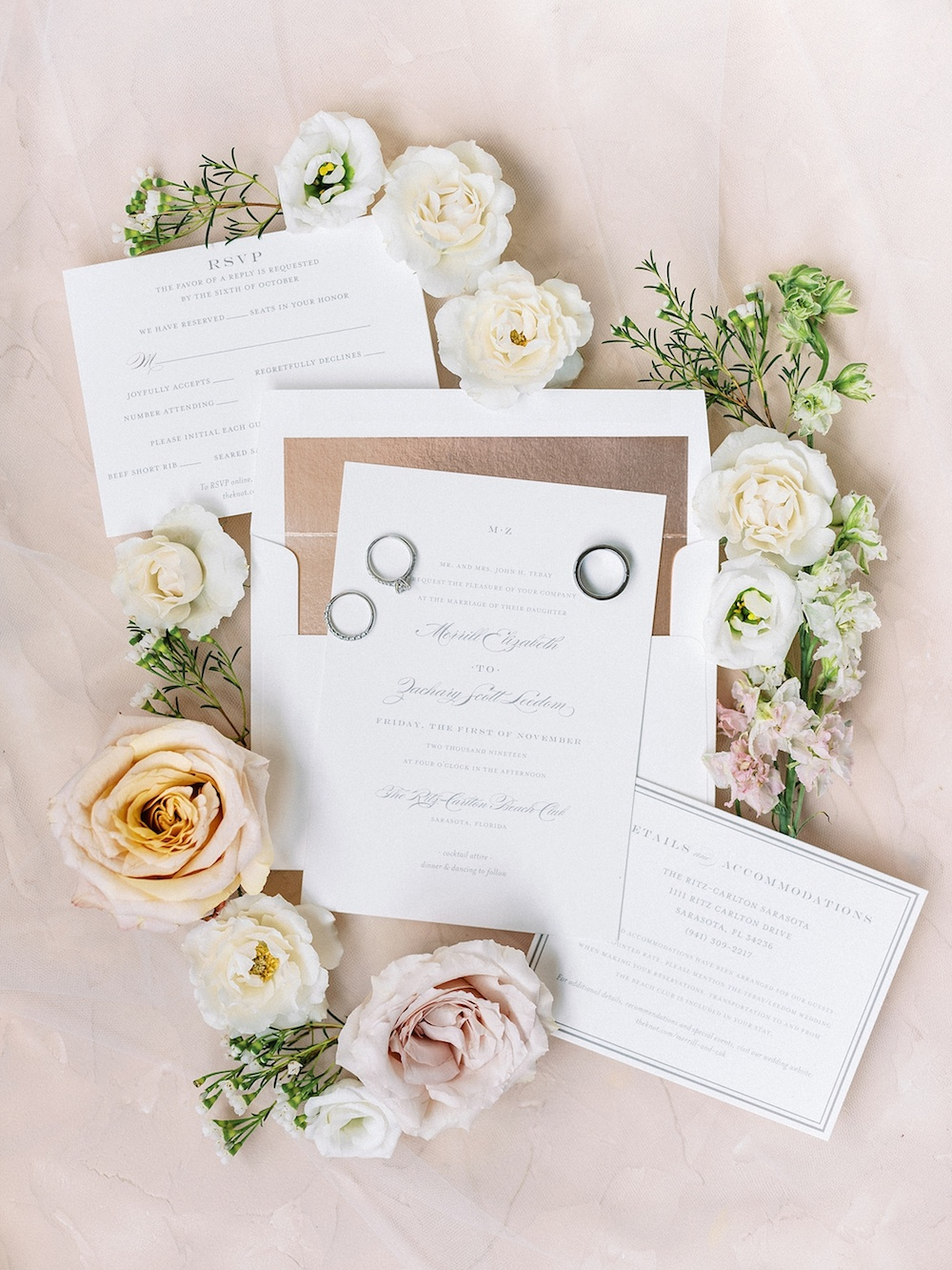 stationery surrounded by flowers and rings